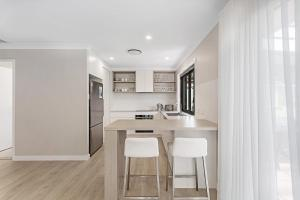 A kitchen or kitchenette at Wirragulla, 10 Marty Avenue - Stylish Modern House with ducted air con & WIFI