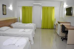 A bed or beds in a room at Muffato Plaza Hotel