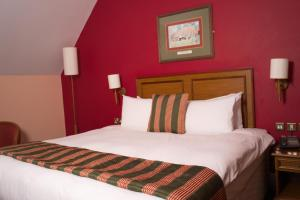 A bed or beds in a room at The Catherine Wheel Wetherspoon Hotel