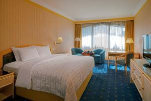 سرير أو أسرّة في غرفة في فندق لو ميريديان هليوبوليس