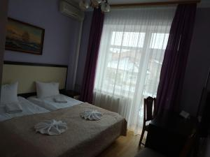 A bed or beds in a room at Pysanka Hotel