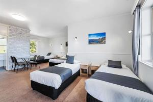 A bed or beds in a room at Coach House Launceston