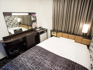 A bed or beds in a room at APA Hotel Hakodate Ekimae