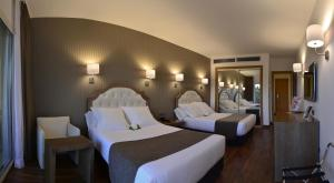 A bed or beds in a room at Beatriz Toledo Auditorium & Spa