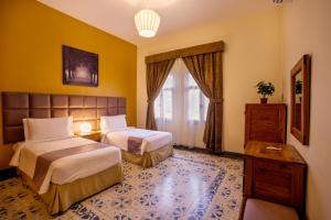A bed or beds in a room at Copthorne Al Jahra Hotel & Resort