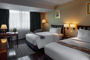 A bed or beds in a room at Mercure Mandalay Hill Resort