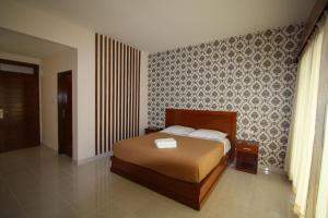 A bed or beds in a room at Suka Beach Inn