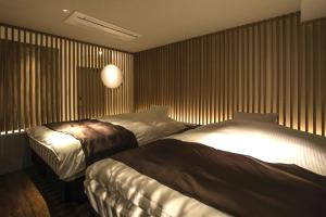A bed or beds in a room at Hotel The Grandee Shinsaibashi