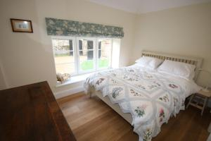 A bed or beds in a room at Bolton's Cottage
