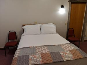 A bed or beds in a room at The BarnwooD Inn