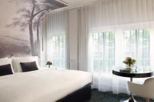 A bed or beds in a room at Renaissance Paris Nobel Tour Eiffel Hotel