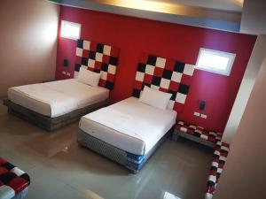 A bed or beds in a room at Suvarnabhumi Trang Resort
