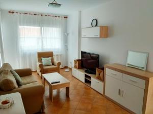 A television and/or entertainment center at Islantilla-Apartamento con piscina y garaje en primera línea de playa