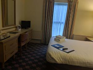 A bed or beds in a room at Best Western Ipswich Hotel