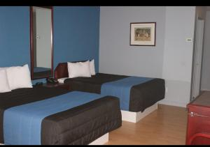 A bed or beds in a room at Motel Le Victo