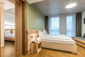 A bed or beds in a room at Green City Hotel Vauban