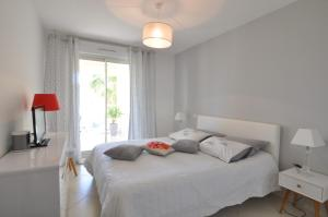 A bed or beds in a room at Elegant one-bedroom apartment with swimming pool - StayInAntibes - Le Vallon