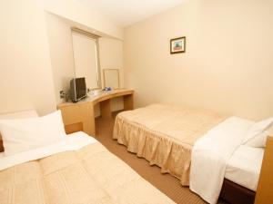 A bed or beds in a room at Hotel Pearl City Tendo