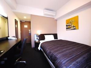 A bed or beds in a room at Hotel Route-Inn Yokohama Bashamichi