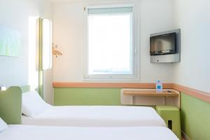 A bed or beds in a room at ibis budget Versailles Chateau Saint cyr l'Ecole