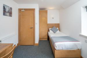 A bed or beds in a room at OYO Flexistay Aparthotel Sutton