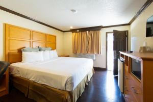A bed or beds in a room at Travelodge by Wyndham Merced Yosemite
