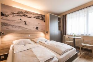A bed or beds in a room at JUFA Hotel Malbun Alpin Resort