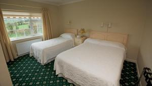 A bed or beds in a room at Ard Na Greine Country House