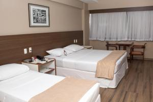 A bed or beds in a room at Pajuçara Praia Hotel