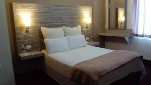 A bed or beds in a room at Hotel Royal Inn