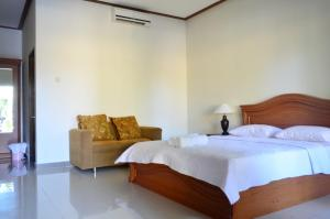 A bed or beds in a room at Puri Anom Guest House