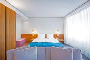 A bed or beds in a room at Lindner Hotel AM KU'DAMM Berlin