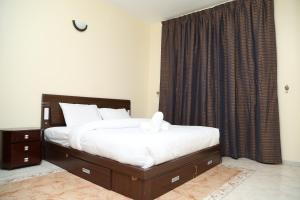 A bed or beds in a room at Safari Hotel Apartments - BAITHANS