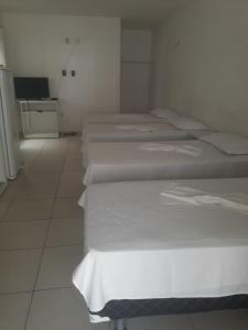 A bed or beds in a room at Pecem suites