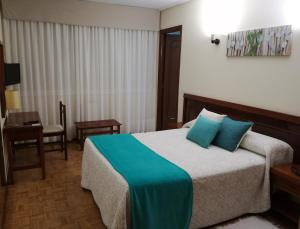 A bed or beds in a room at Hotel Almendra