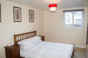 A bed or beds in a room at Bright 2 Bedroom Flat with Patio