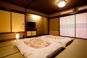 A bed or beds in a room at Dantokan Kikunoya