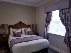 A bed or beds in a room at The Atherstone Red Lion Hotel