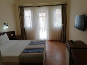 A bed or beds in a room at Karbel Beach Hotel
