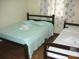 A bed or beds in a room at Pousada Laura / Ziza
