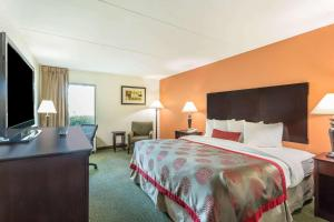 A bed or beds in a room at Ramada by Wyndham Luling