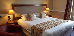 A bed or beds in a room at Cahir House Hotel