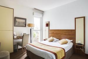 A bed or beds in a room at Brit Hotel De La Côte Des Havres
