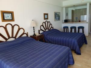 A bed or beds in a room at Salvia Cancun Aparts