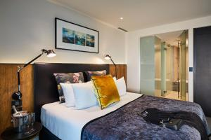 A bed or beds in a room at The Grand by SkyCity