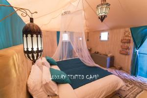 A bed or beds in a room at Luxury Tented Camp
