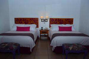A bed or beds in a room at Boutique Pueblo Lindo