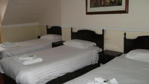 A bed or beds in a room at Patten Arms Hotel
