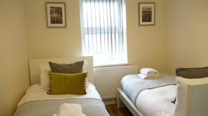 A bed or beds in a room at Heathrow Ensuite Rooms