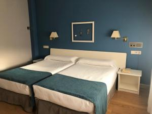 A bed or beds in a room at Hotel Jakue